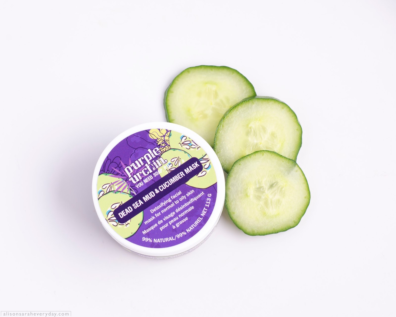 Purple Urchin Dead Sea Mud & Cucumber Mask with the lid on displayed on a white background with cucumber slices