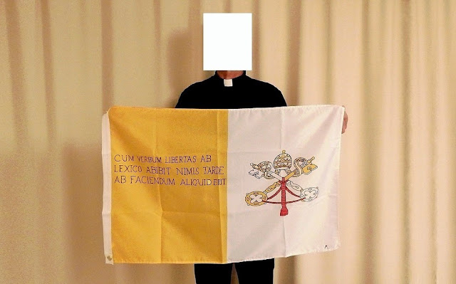 Padre Marcelo and his flag with the sentence in Latin.