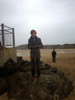 standing on a rock formation on a cornish beach