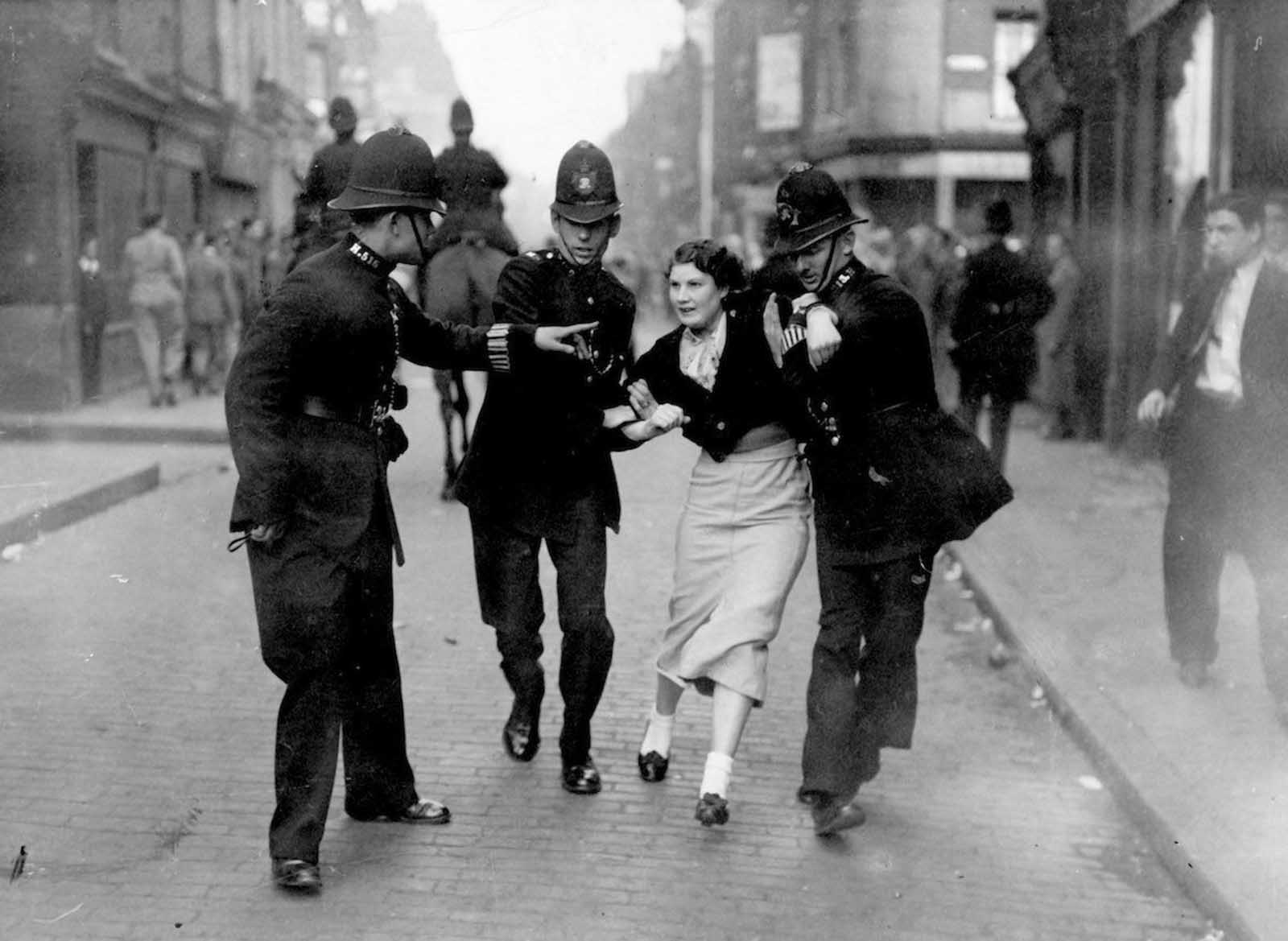 Policemen arresting a demonstrator when Fascists and Communists clashed during a march led by British Fascist Oswald Mosley in London's East End. 1936.