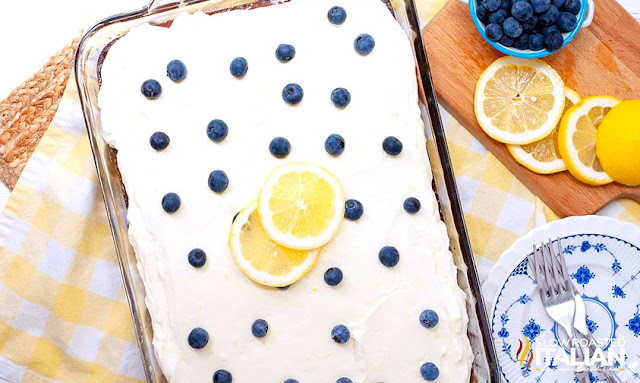 pan of blueberry cake topped with whipped cream cheese frosting