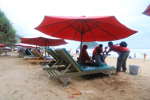 duduk santai di bawah payung merah
