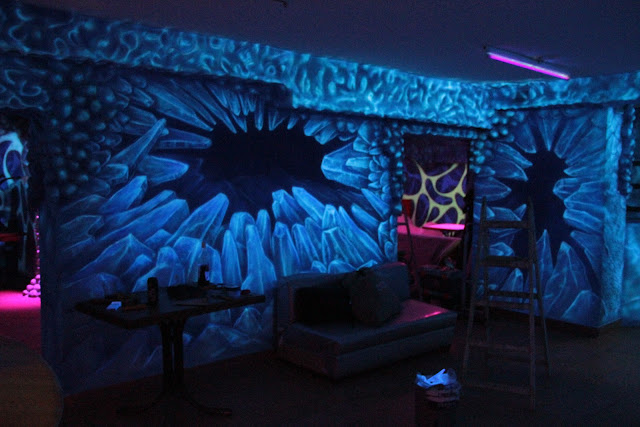 Malowanie ścian w dyskotece farbami fluorescencyjnymi świecącymi w ciemności, mural UV