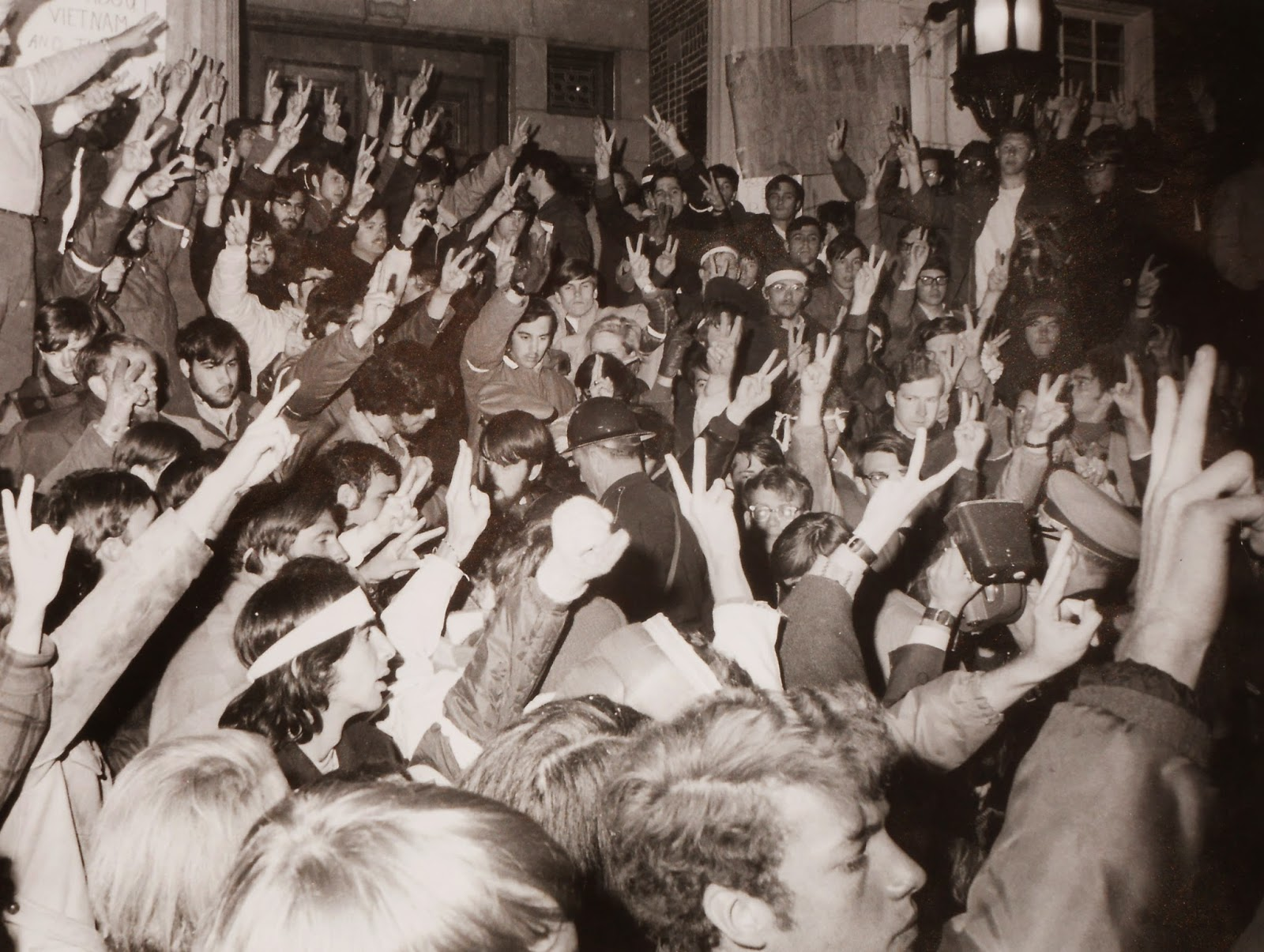A black and white photograph of a dense crowd of people throwing up peace signs.
