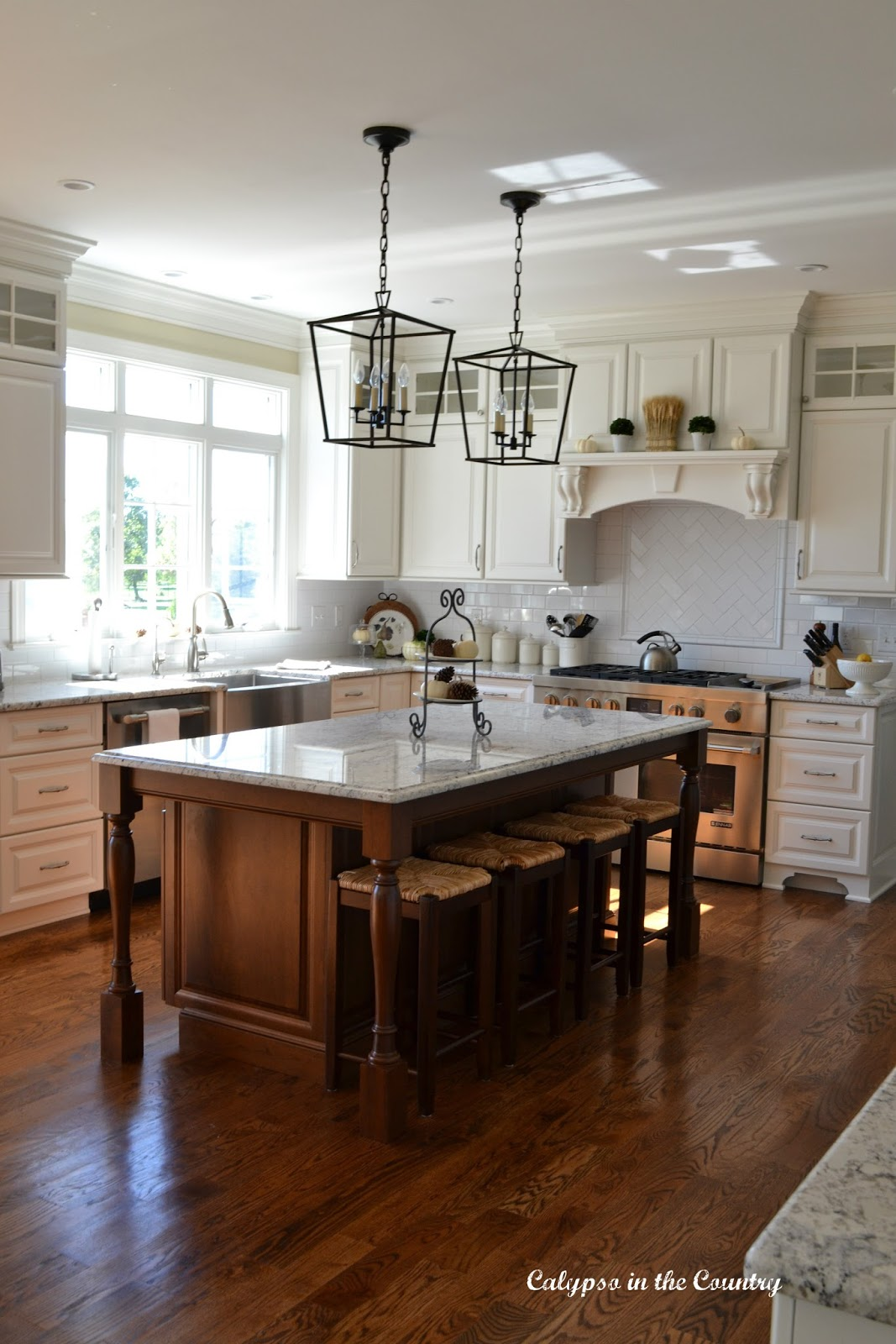 White kitchen with cherry island and matching counter stools