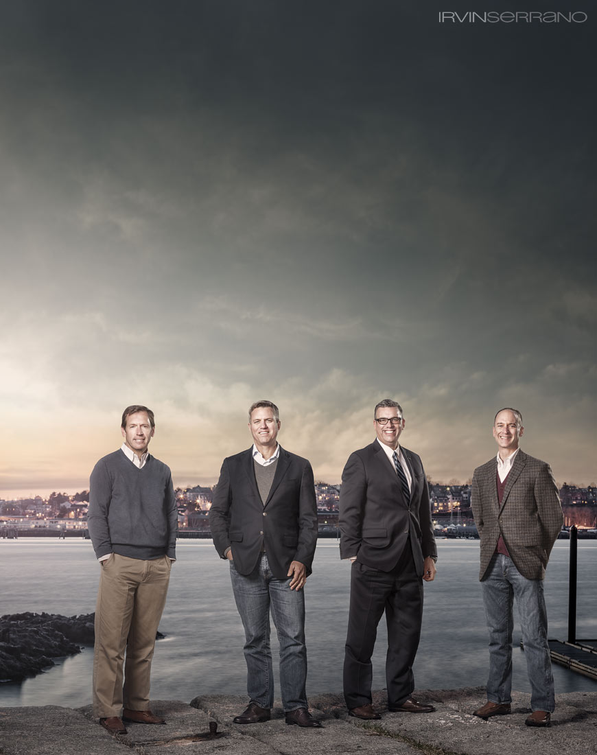 Four business men, hotel developers, stand in front of Casco Bay and the city of Portland's skyline at dusk.