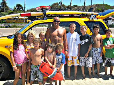 Group of Aloha Beach Camp pose for a group picture with Los Angeles County Lifeguard Captain Remy Smith and his lifeguard truck at Zuma Beach