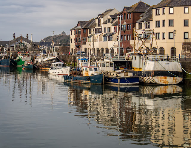 Photo of rippled reflections of some of the fishing boats in Maryport harbour