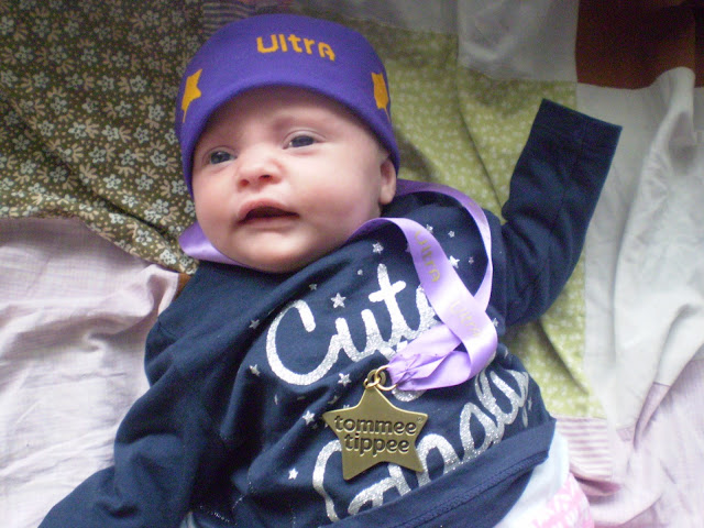 Baby in headband with medal ready for the Ultra Games