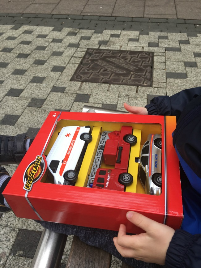Our-Weekly-Journal-Grandad's-New-Hip-toddler-with-new-toy-in-box-ambulance-fire-engine-and-police-car