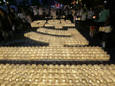"Prayers ... South Korean Buddhists put candles to form the words meaning ""Together"", for"