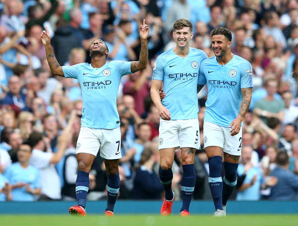 Raheem Sterling of Manchester City celebrates after scoring his team's first goal with Kyle Walker of Manchester City and John Stones of Manchester City during the Premier League match between Manchester City and Newcastle United at Etihad Stadium on September 1, 2018 in Manchester, United Kingdom.