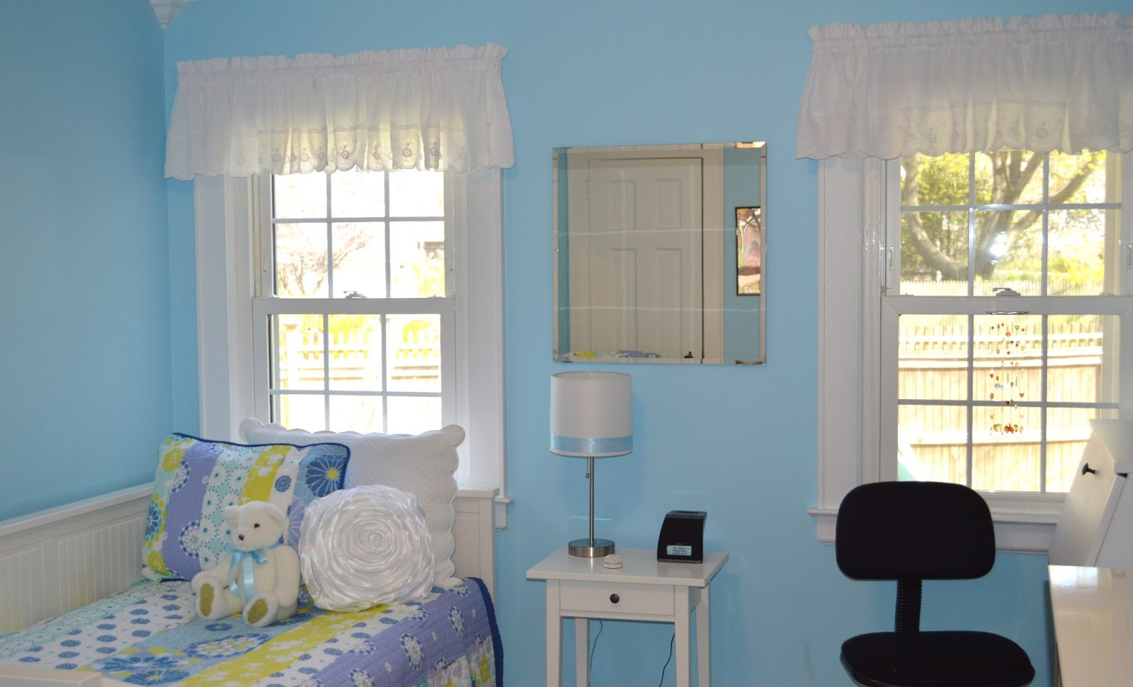 Blue and White Girls's Bedroom with teddy bear on bed