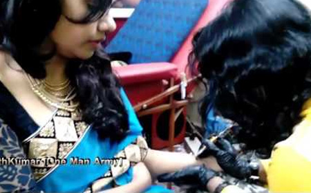 A Female fan of Thala Ajith inks his face as Tatoo