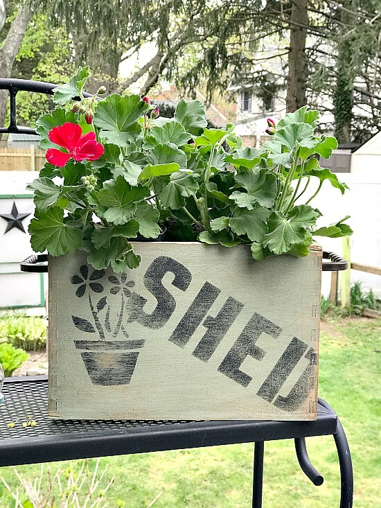 Rustic stenciled flower box to hold flowers in the yard.