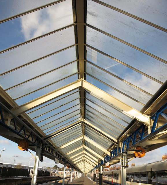 Seeing blue sky through glass roof at railway station.