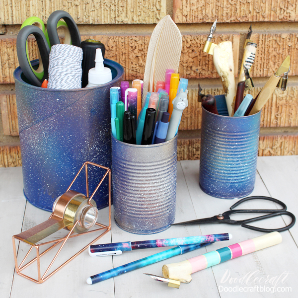 Galaxy Painted Pen Holders  Save those soup cans and turn them into pen holders! Add some paint or spray paint for the perfect galactic finish.