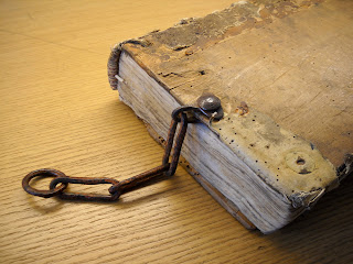 A photograph of a book with a few chain links attached to its edge.
