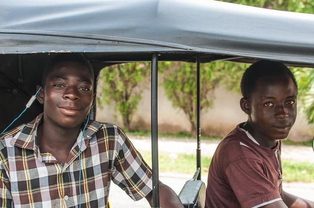 Teenage boys riding in a tuk-tuk or three-wheeled taxi in Abuja Nigeria