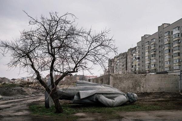Imagen de la caída del comunismo en Ucrania: estatua de Lenin derribada al lado de un árbol y frente a edificios.