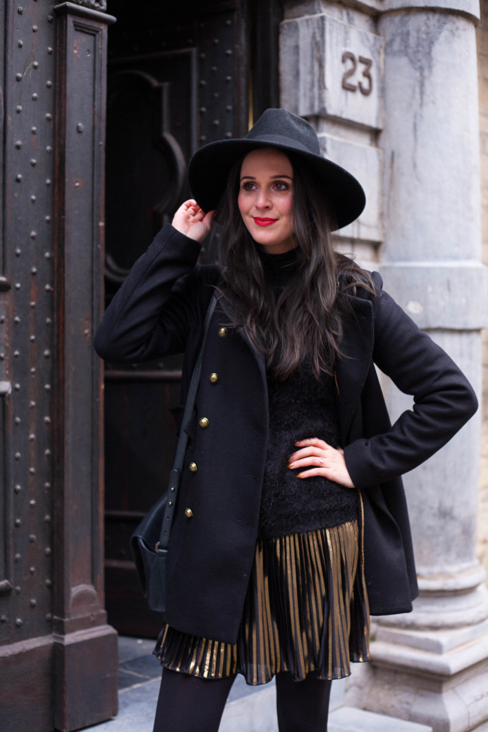 Outfit: wide brim hat, military coat, gold pleated skirt