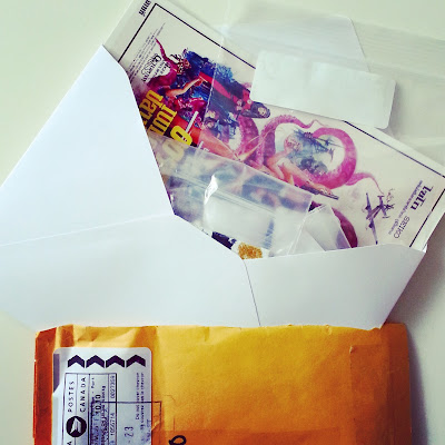 Opened bubble bag with an envelope sticking out of it. Inside the envelope is a Bollywood film poster card, and a number of small zip-lock bags.