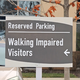 grey sign, reads reserved parking on first line, walking impaired visitors with an arrow pointing backwards on the second