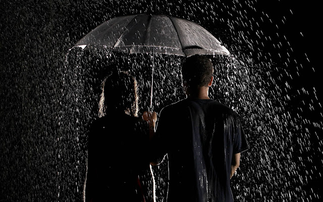Jongen en meisje in de regen met paraplu in het donker
