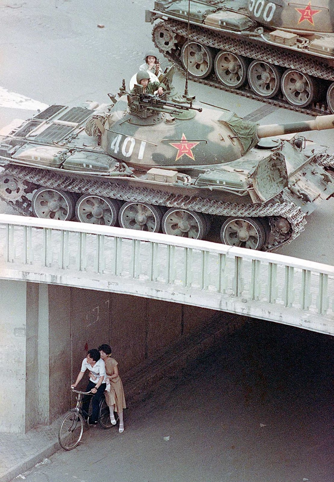 A Chinese couple on a bicycle take cover beneath an underpass as tanks deploy overhead in eastern Beijing, on June 5, 1989.