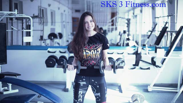 A beautiful girl doing body workout with dumbbells in gym