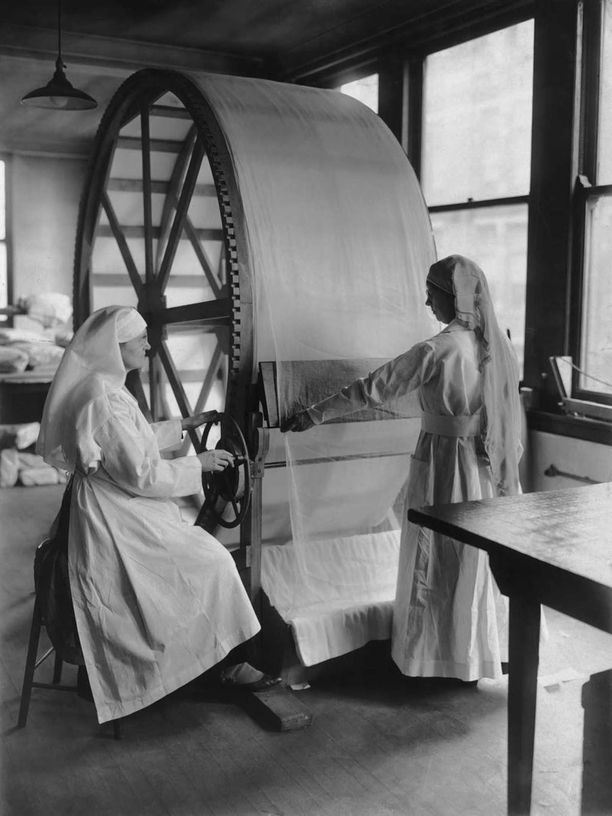 Las mujeres operan la nueva máquina de estiramiento para vendajes quirúrgicos en la sede de la Cruz Roja en Cincinnati, Ohio, alrededor de 1915.