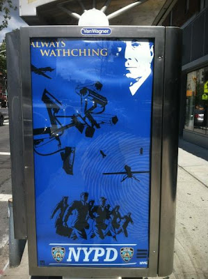 Blue poster in transit kiosk, with white image of Michael Bloomberg, cameras, and police in uniform with headline ALWAYS WATHCHING and the NYPD logo at bottom