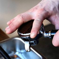tamping espresso grounds