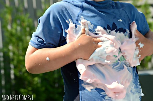 Kid rubbing colored shaving cream on their body