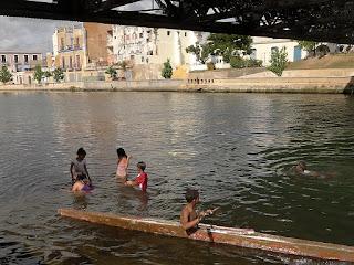 Kuba, Matanzas, Kinder spielen im Wasser des Rio St. Juan unter  unter der Brücke Puente Calixto Garcia im Schatten.