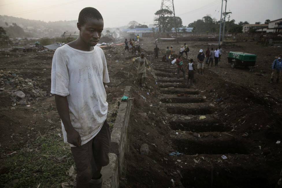 A grave digger looks at freshly dug graves for Ebola victim at a cemetery in Freetown, Sierra Leone, December 17, 2014. REUTERS/Baz Ratner