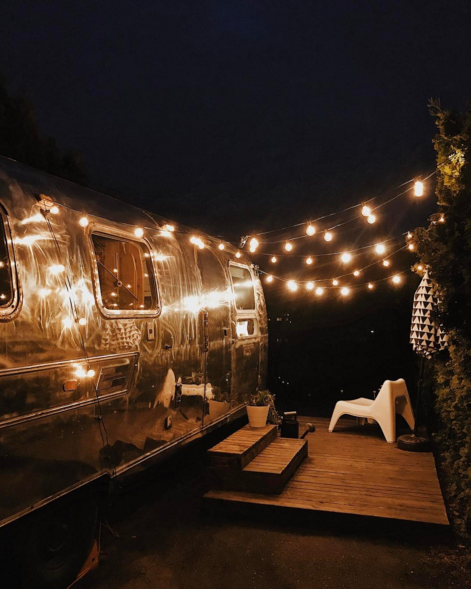 all silver vintage airstream with a beautiful outdoor patio area with string lights at night