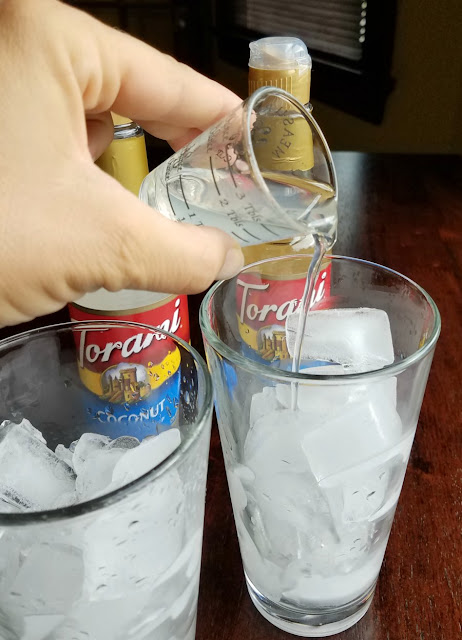 tall glasses of ice with hand pouring clear liquid overtop