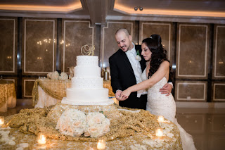 Couple Cutting The Cake With Smiles