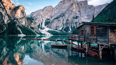 Paisaje sorprendente con lago, casa de madera, montañas y arboles