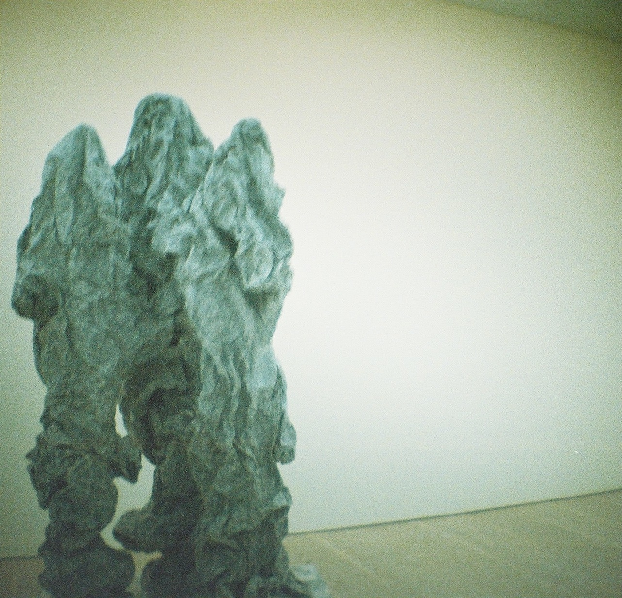A sculpture which looks like a lump of crumpled paper shaped into three distinct figures like people wearing crumpled sheets.