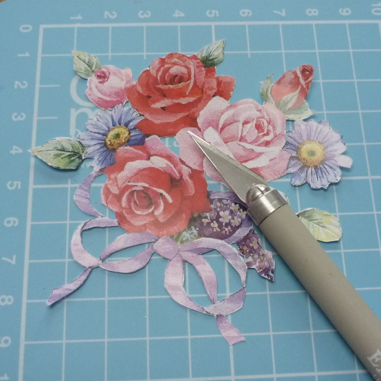 Cutting out white sections of printed design with a craft knife on a cutting mat