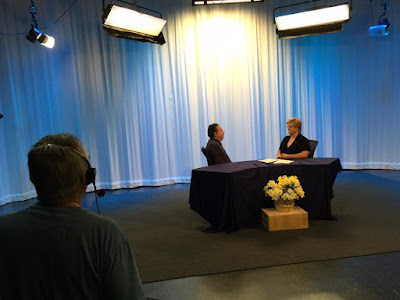 A view from behind the cameras program 2 of 'Blindside Fresno' is being recorded a pale blue and white background leaves guest Nathan Romo president of fresno chapter California council of the blind and host Darcie Elliott in a near silohuette