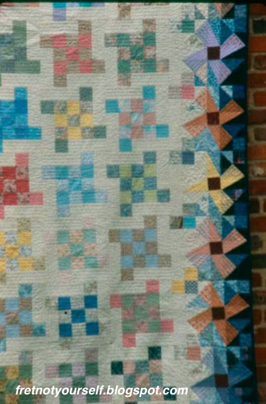 Detail of quilt  with Flying Squares blocks made of light and medium prints on muslin with a border shading from light to dark made of Crazy Ann blocks