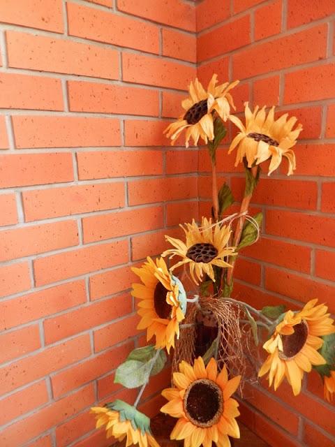 Bukiet słoneczników w ceglanym ganku