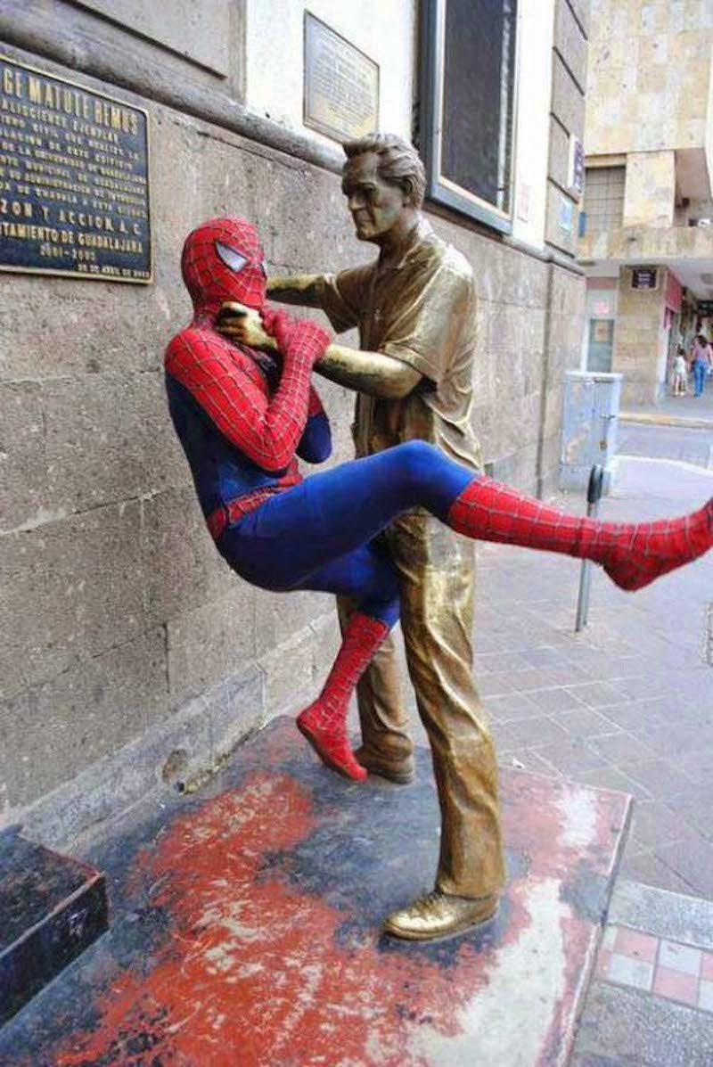 4. For a moment this image makes you think: who is the statue? A closer look proves spiderman is real and the whole city is in danger if he doesn't stop messing around! - 23 Times Pedestrians Messed With Statues...And It Was Downright Hilarious