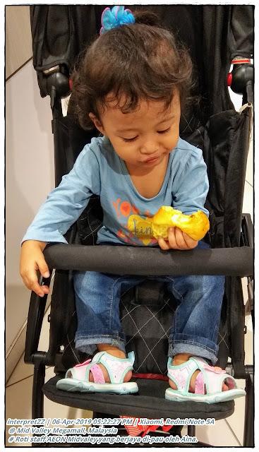 Gambar kanak-kanak perempuan 2 tahun duduk atas stroller sambil makan roti.