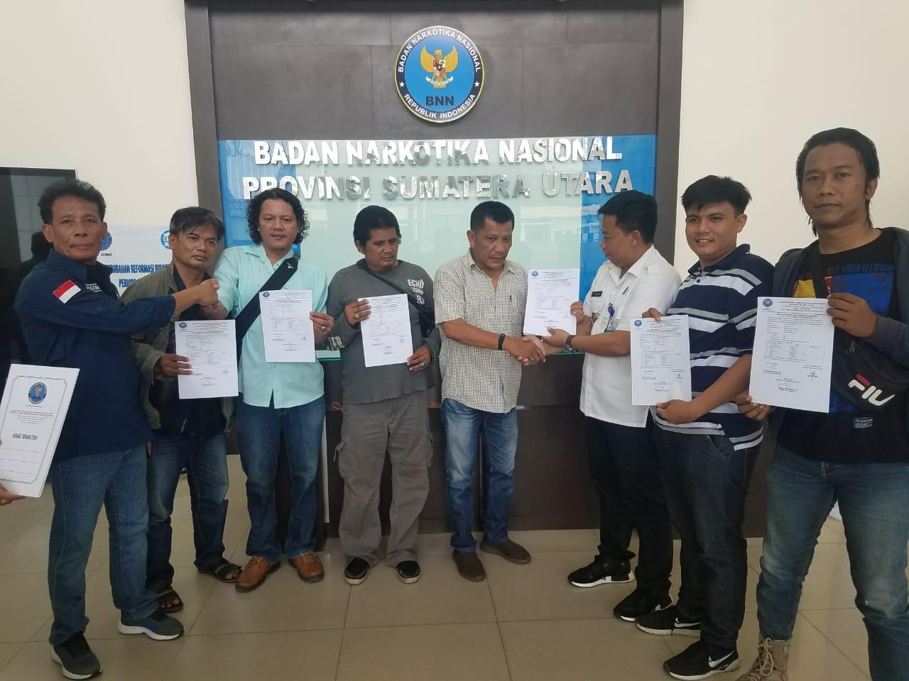 SERAHKAN: Kabid Pemberantasan Narkotika BNNP Sumut AKBP Agus Halimudin saat menyerahkan surat bebas narkoba ke Ketua Wartawan Unit Polrestabes Medan, Iwan Suherman.