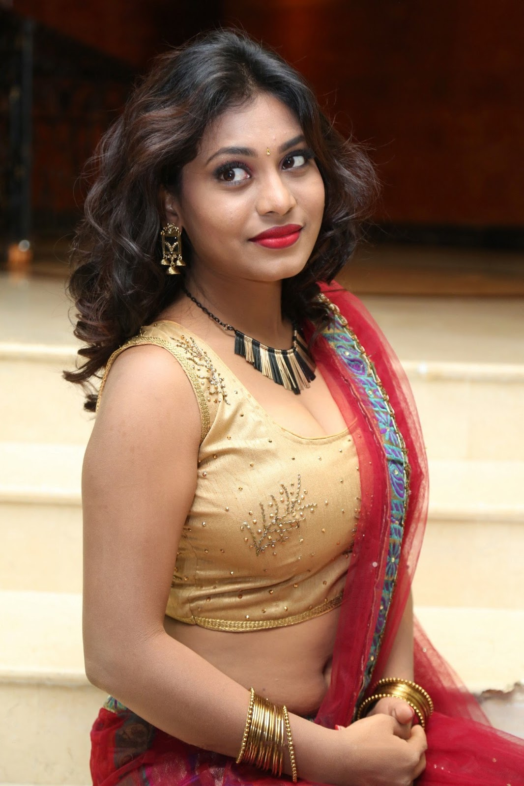 Priya Augustin Looks Stunning in Sleeveless Choli and Red Saree