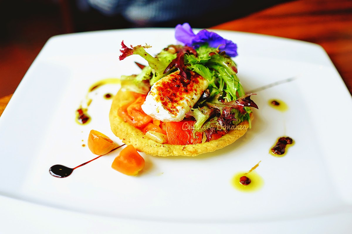 Fresh Goat Cheese Salad, Roasted vegetable salad served on savoury tartlet with lentil dressing and topped with edible flowers